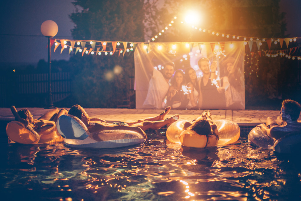 Young friends having pool movie night party. Floating on the pool on inflated mattresses and watching movie on improvised screen. Backyard decorated with festive string lights. Night time.
